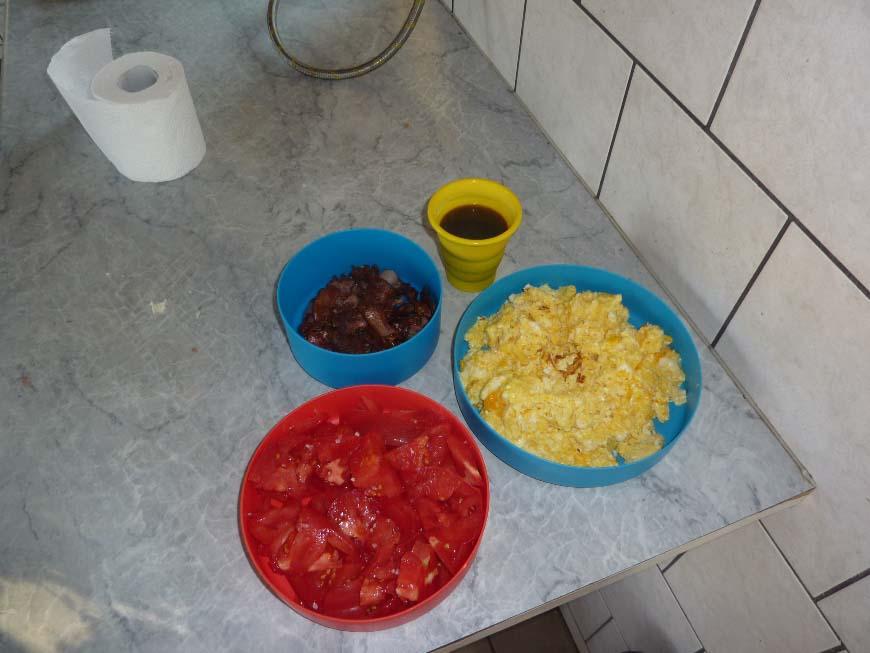 Śniadanie: jajecznica, boczek i pomidor surowy.