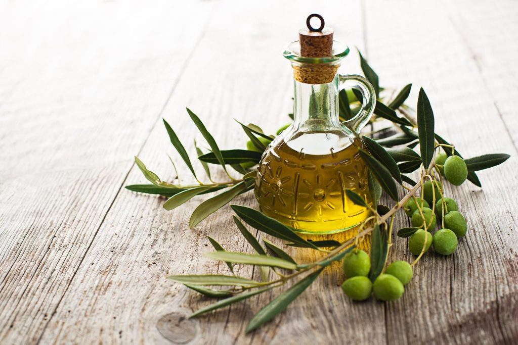 Olive oil and olive branch on the wooden table